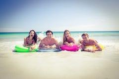 Amis heureux se trouvant sur le matelas gonflable au-dessus de l'eau Images stock