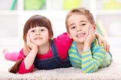 Amis heureux se trouvant sur le plancher Image libre de droits