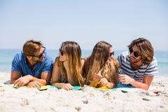 Amis heureux se trouvant sur le sable à la plage Photo libre de droits