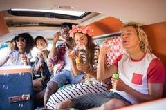 Amis heureux soufflant des baguettes magiques de bulle dans le camping-car Photo libre de droits