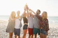 Amis heureux soulevant des bouteilles à bière Photographie stock libre de droits