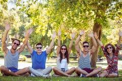 Amis heureux soulevant leurs mains en parc Photo libre de droits