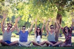 Amis heureux soulevant leurs mains en parc Image libre de droits