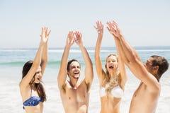 Amis heureux soulevant leurs mains sur la plage Image libre de droits