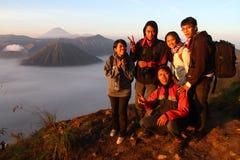 Amis heureux souriant en haut d'une montagne Photo stock