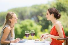 Amis heureux souriant tout en ayant la nourriture Photographie stock libre de droits