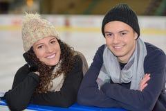 Amis heureux sur la piste de patinage Photos libres de droits
