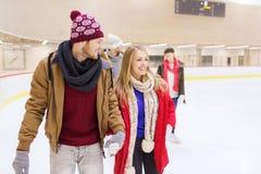 Amis heureux sur la piste de patinage Photographie stock