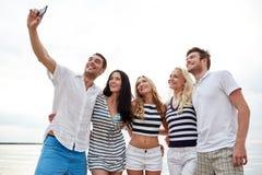 Amis heureux sur la plage et le selfie de prise Photo libre de droits