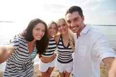 Amis heureux sur la plage et le selfie de prise Photos libres de droits