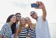 Amis heureux sur la plage et le selfie de prise Photographie stock