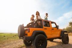 Amis heureux sur un voyage par la route se tenant dans une voiture convertible Image stock