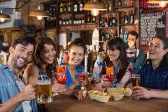 Amis heureux tenant des boissons à la table Images stock