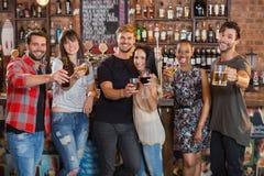 Amis heureux tenant des boissons Photographie stock libre de droits