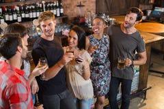 Amis heureux tenant des boissons dans la barre Photographie stock libre de droits