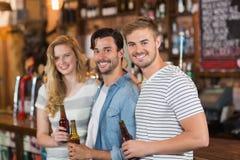 Amis heureux tenant des bouteilles à bière au bar Photographie stock libre de droits