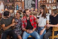 Amis heureux tenant des bouteilles à bière et des verres à vin Image libre de droits