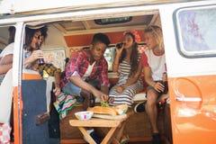 Amis heureux tenant des bouteilles à bière tout en se reposant dans le camping-car Photos libres de droits