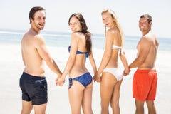Amis heureux tenant des mains ensemble sur la plage Images libres de droits