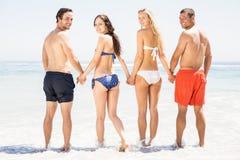 Amis heureux tenant des mains ensemble sur la plage Photo libre de droits