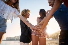 Amis heureux tenant des mains ensemble sur rire de plage Images libres de droits