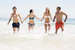 Amis heureux tenant des mains et le fonctionnement sur la plage Images stock