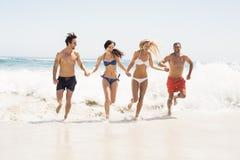 Amis heureux tenant des mains et le fonctionnement sur la plage Photos stock