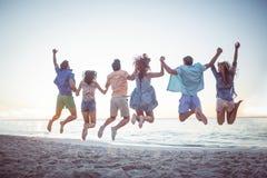 Amis heureux tenant des mains et sauter Photos libres de droits