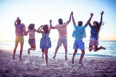 Amis heureux tenant des mains et sauter Images libres de droits