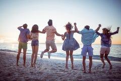 Amis heureux tenant des mains et sauter Photographie stock libre de droits