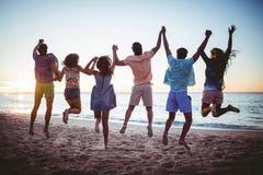 Amis heureux tenant des mains et sauter Photographie stock