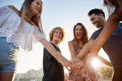 Amis heureux tenant des mains riant ensemble au soleil Images libres de droits