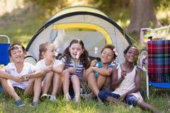 Amis heureux tenant des sucreries par la tente au terrain de camping Photographie stock