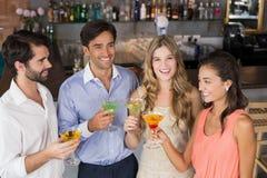 Amis heureux tenant des verres de cocktail Photos stock
