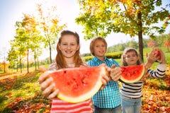 Amis heureux tenant la pastèque et la consommation Photo stock