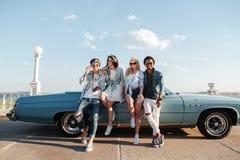 Amis heureux tenant la voiture proche de vintage Image stock