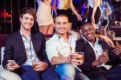 Amis heureux tenant le verre d'alcool Photo stock