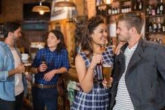 Amis heureux tenant le verre et la bouteille de bière dans le bar Photos libres de droits