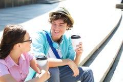 Amis heureux tenant les tasses de café jetables tout en se reposant sur des étapes dehors Photographie stock libre de droits