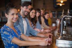 Amis heureux tenant les verres courts sur le compteur dans la barre Photographie stock libre de droits