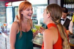 Amis heureux tenant un cocktail devant le compteur de barre Photographie stock libre de droits