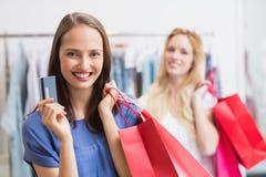 Amis heureux tenant une carte de crédit Photo stock