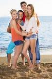 Amis heureux très étroits à la plage Image libre de droits