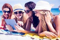 Amis heureux utilisant des lunettes de soleil et à l'aide du comprimé Photographie stock