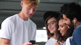 Amis heureux utilisant le téléphone portable au parking banque de vidéos