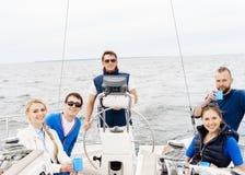 Amis heureux voyageant sur un yacht et buvant d'un thé Image stock