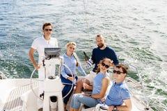 Amis heureux voyageant sur un yacht et un champagne potable Photographie stock libre de droits