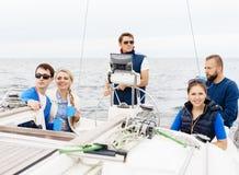 Amis heureux voyageant sur un yacht et un thé potable Photographie stock