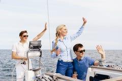 Amis heureux voyageant sur un yacht et un thé potable Photos stock