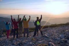 Amis heureux, voyageurs, avec les bras ouverts dans les montagnes Images stock